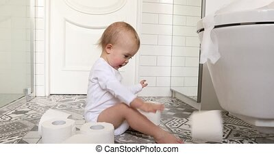 Toddler playing with toilet paper sitting on floor - Toddler...