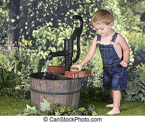 Toddler Scrubbing Bricks by the Water Pump