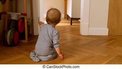 Toddler sitting by doorway - Toddler opens and closes the...