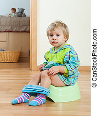 Toddler sitting on green potty in home interior