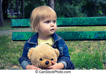 Toddler sitting on the bench in the park