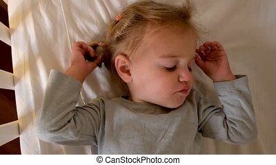 Toddler sleeping on cot at home - From above cute little ...