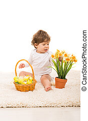 Toddler with easter eggs and narcissus