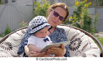 Toddler with grandmother holding tablet. Happy family concept. Grandmother with granddaughter.