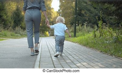 Toddler with his mom walking in the park