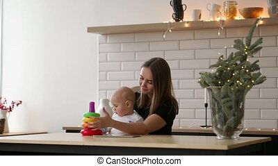 Toddler with mom playing with the toy in nursery room....