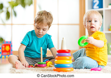 Toddlers kids playing with wooden blocks at home