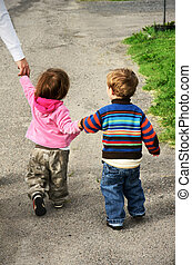 Vertical of two colorful toddlers walking away holding hands with an adult woman out of frame on the side of the road.