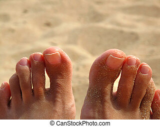 Toes in sand, bare feet on sand beach