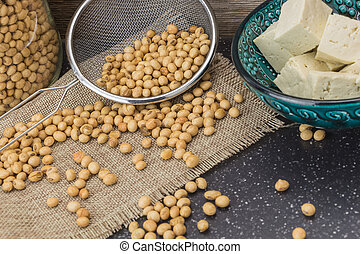 Tofu cut into cubes and soybeans, on wooden background.