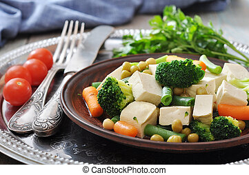 Tofu with boiled vegetables on plate and tomatos closeup