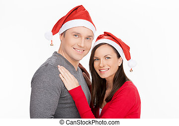 Together at Christmas Eve. Cheerful young couple in Santa hat holding standing close to each other and smiling while standing isolated on white