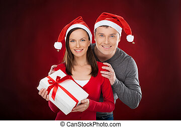 Together at Christmas Eve. Cheerful young couple in Santa hat holding a gift box and smiling while standing isolated on red