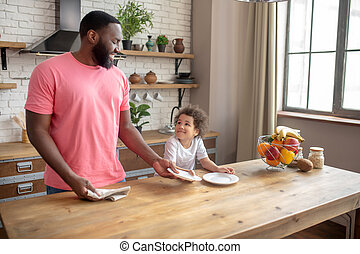 Tall dark-skinned man in a pink tshirt giving a plate to his kid for wiping