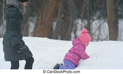 Together mother with cute little daughter enjoying winter weather in the park