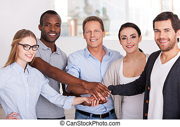 Together we are stronger! Group of cheerful business people in casual wear standing close to each other and holding hands together