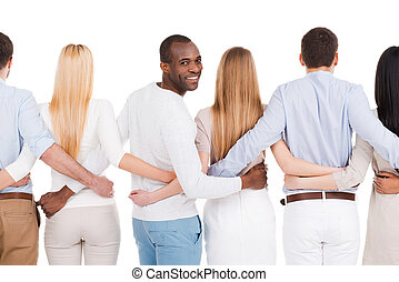 Together we are stronger! Rear view of group of diverse people bonding to each other and standing against white background while one African man looking over shoulder and smiling