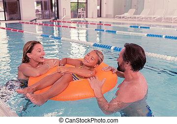 Delighted nice girl having fun in the pool