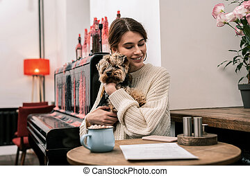 Woman hugging her dog while sitting in a cafe