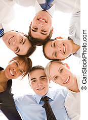 Below view of happy businesspeople making circle against white background