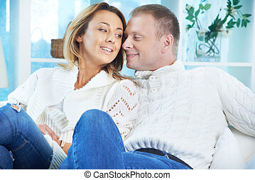 Togetherness - Happy couple in white pullovers and jeans...