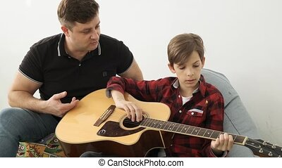 Togetherness in learning how to play guitar between father...