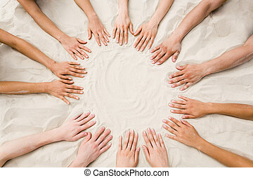 Togetherness - Image of several hands on sand in the form of...
