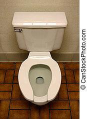 a bathroon toilet against a tiled wall and tiled floor