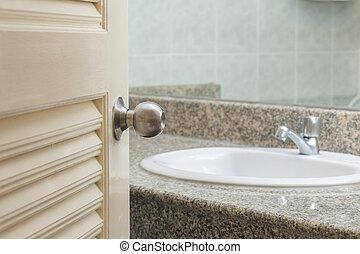 Toilet door open with sink