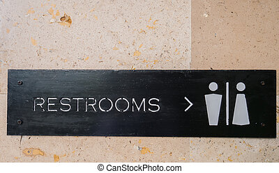 toilet or rest room sign on the wall.