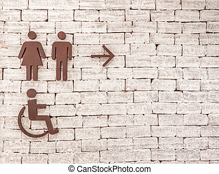 Toilet or restroom sign and symbol for woman and man with person on wheelchair on white brick wall background