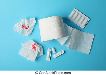 Toilet paper, candles and paper with blood on blue background, top view