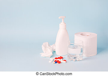 Toilet paper roll, sanitizer antiseptic gel, pills, glass of water on blue background. People are stocking up essentials for home quarantine. Consumer buying panic about coronavirus covid-19 concept