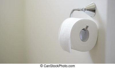 Toilet Paper Roll - Person unrolls toilet paper tissue in...