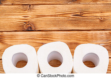 Toilet paper rolls on wooden background top view