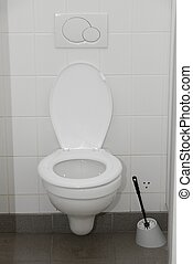 Toilet with white, tiled wall