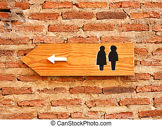 Toilet sign and direction on brick wall