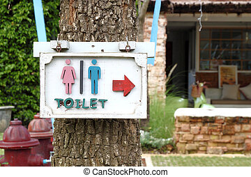 toilet sign on the tree