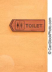 Toilet wood label on orange wall.