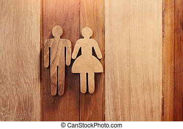 toilets sign icon for women and man (wood texture) on wooden background