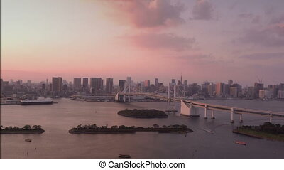 Tokyo skyline with Tokyo Tower and Rainbow Bridge at sunset in Tokyo, Japan
