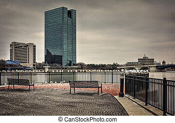 A panoramic view of downtown Toledo Ohio's skyline from across the Maumee river at a popular restaurant area with a paver brick boardwalk and a decorative iron railing.. A stormy cloud filled sky for a backdrop.