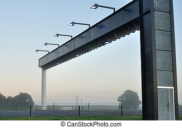 Electronic toll gate in morning fog, tree silhouettes