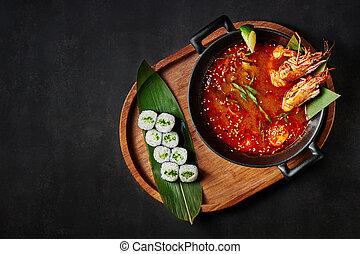 tom yum soup with maki roll at black background