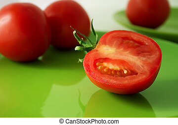 Tomato - A half of tomato on a green plate