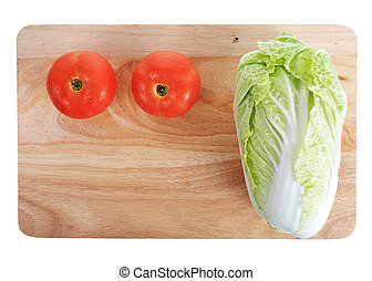 tomato and cabbage on wooden chopping board with water drops