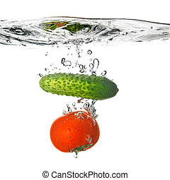 tomato and cucumber dropped into water isolated on white