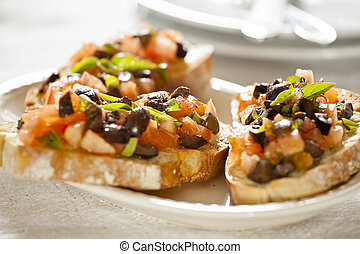 Tomato and Olives Bruschetta Entree - Close up photograph of...