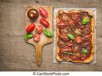 Tomato cake with fresh basil and thyme and selection of fresh tomatoes on a wooden board over a sackcloth surface