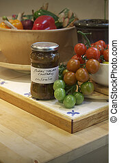 Tomato Chutney - A kitchen setting with a white ceramic bowl...